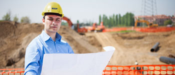 Guy holding a engineering drawing on a job site