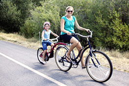 mother and daughter biking along side of road